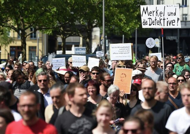 Participants of a demonstration protest in Berlin, Saturday Aug. 1, 2015. Banner at right reads Merkel und die Detektive! (lt: Merkel and the detectives).
