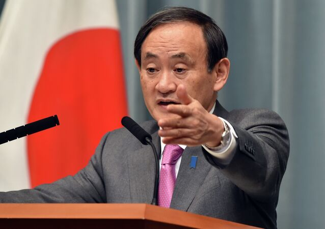 Japan's Chief Cabinet Secretary Yoshihide Suga points to a journalist at a press conference