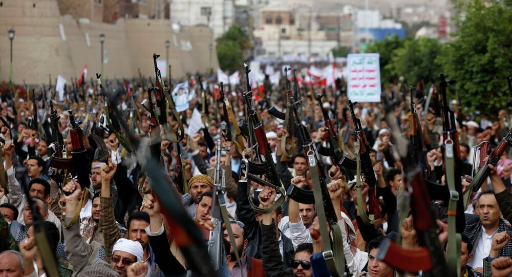 Shiite rebels known as Houthis hold up their weapons as they chant slogans during a rally against Saudi-led airstrikes in Sanaa, Yemen.