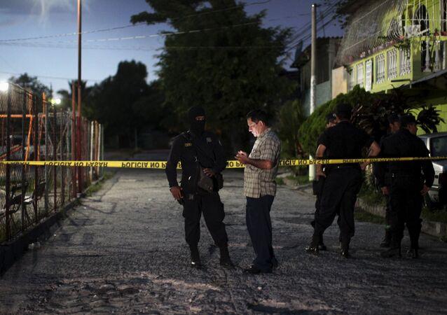 Policemen guard the crime scene where five men were murdered at a soccer field in Cuscatancingo, El Salvador August 2, 2015