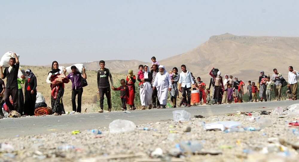 A file picture taken on August 13, 2014, shows displaced Iraqi families from the Yazidi community crossing the Iraqi-Syrian border at the Fishkhabur crossing, in northern Iraq