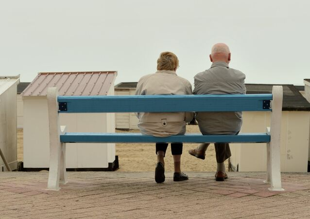 This picture taken on July 16, 2015 shows a couple of elderly people sitting on a bench in Calais, northern France