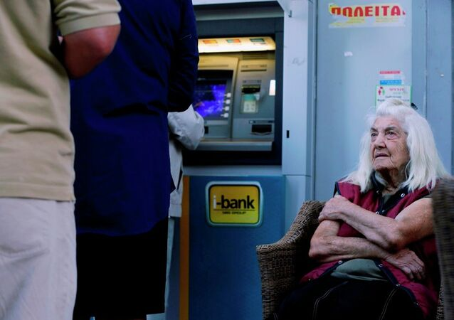 A pensioner looks at customers who use an ATM as she sits outside a bank in Athens, Wednesday, July 1, 2015.