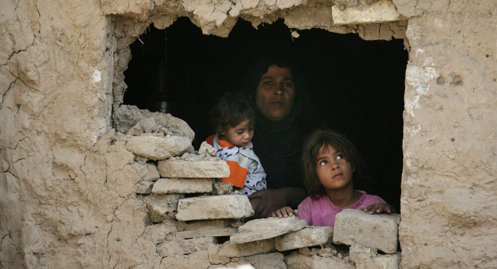 Iraqi family stands inside their home hit by an airstrike in Fidhailiya area in eastern Baghdad, Iraq.