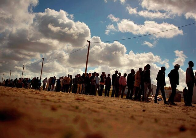 Migrants line up as the wait for a food ration distributed by the Banque Alimentaire of Calais at a camp in northern France, Tuesday, Aug. 4, 2015.
