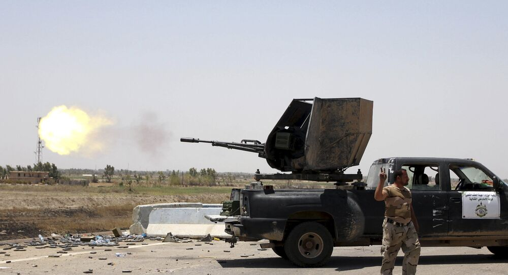 A Shi'ite fighter from Hashid Shaabi forces fire toward Islamic State militants in the town of Saqlawiyah, near Falluja, Iraq August 4, 2015