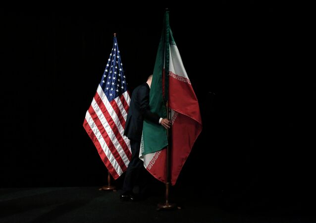 A staff member removes the Iranian flag from the stage after a group picture with foreign ministers and representatives of Unites States, Iran etc.