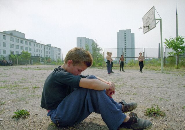 A boy sits by himself on the playground as other boys play in the background.