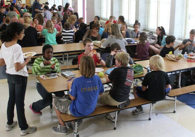 Students eat lunch at a school cafeteria.