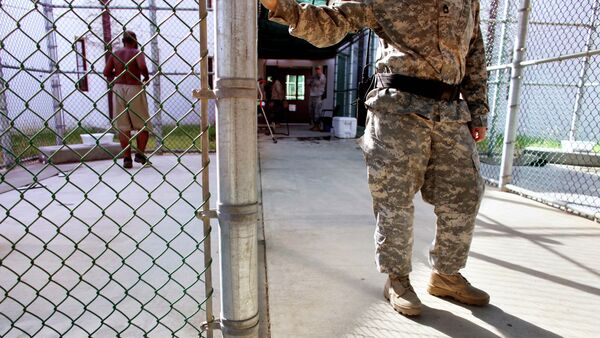 In this photo, reviewed by the US Military, a guard leans on a fencepost as a Guantanamo detainee, left, jogs inside the exercise yard at Camp 5 detention center, the U.S. Naval Base, in Guantanamo Bay, Cuba, January 21, 2009 - Sputnik International