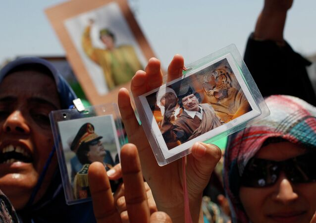 In this file photo taken on a government-organized tour Libyan women show their badges with portraits of Moammar Gadhafi and his son Seif al-Islam as they rally at the Green Square in downtown Tripoli, Libya, on Thursday, June 23, 2011