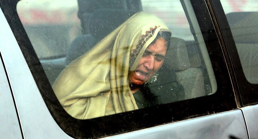 An Afghan woman cries at the site of a suicide attack in Kabul, Afghanistan Monday, Jan. 5, 2015.