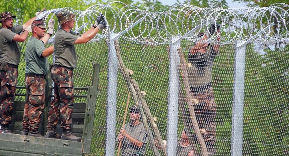 A picture is taken on July 18, 2015 shows soldiers of the Hungarian Army's technical unit finish the first completed elements of the 150 meter-long metal fence at the Hungarian-Serbian border nearby Morahalom village.