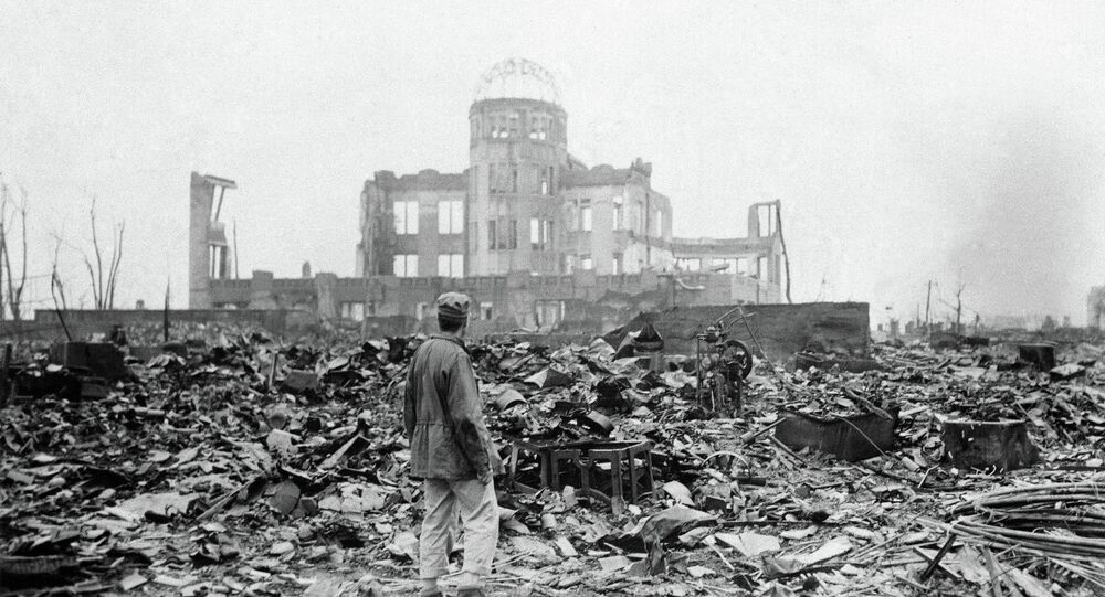 An allied correspondent stands in the rubble in front of the shell of a building that once was a movie theater in Hiroshima, Japan, a month after the first atomic bomb ever used in warfare was dropped by the U.S. on Aug. 6, 1945