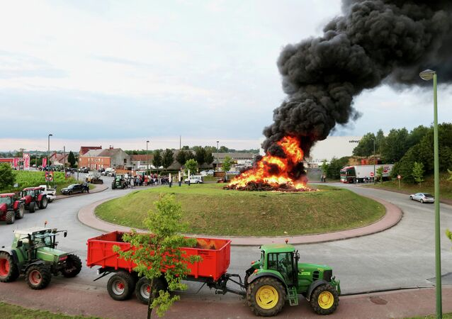 Tractors are parked around a roundabout with a fire burning in the middle during demonstration by dairy farmers on July 29, 2015 in Ghislenghien