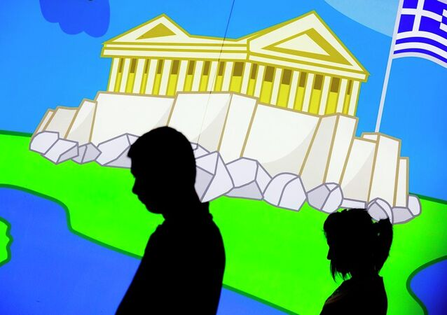 A couple walk in front of a picture displaying the Parthenon, an iconic ancient temple, and the Greek flag in central Athens, Thursday, June 25, 2015.