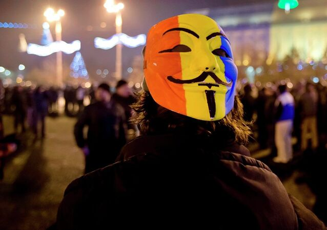 A protester wears a Guy Fawkes mask painted in Romania's flag colors.