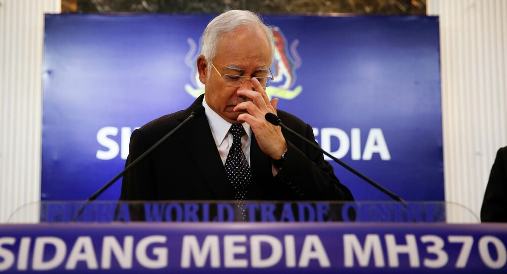 Malaysian Prime Minister Najib Razak, center, gestures before speaking at a special press conference announcing the findings for the ill fated flight MH370 in Kuala Lumpur, Malaysia, early Thursday, Aug. 6, 2015