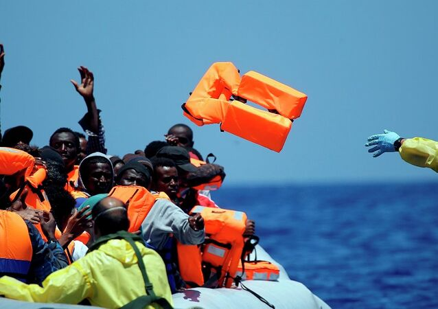 A Belgian nav.y sailor passes life vests to migrants sitting in a rubber boat as they approach the Belgian Navy Vessel Godetia during a search and rescue mission in the Mediterranean Eea off the Libyan coasts, Tuesday, June 23, 2015