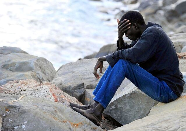 A migrant sits on rocks by the sea