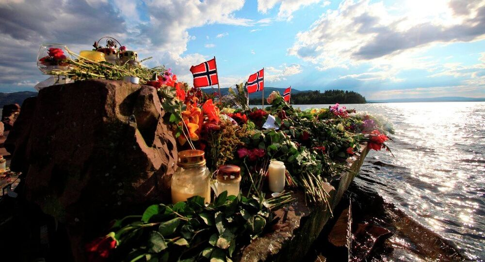 Norwegian flags and flowers are seen in Sundvollen, close to Utoya island, background, where gunman Anders Behring Breivik killed at least 68 people, near Oslo, Norway