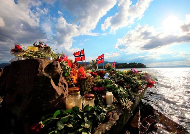 Norwegian flags and flowers are seen in Sundvollen, close to Utoya island, background, where gunman Anders Behring Breivik killed at least 68 people, near Oslo, Norway (Foto vom 28.07.11).