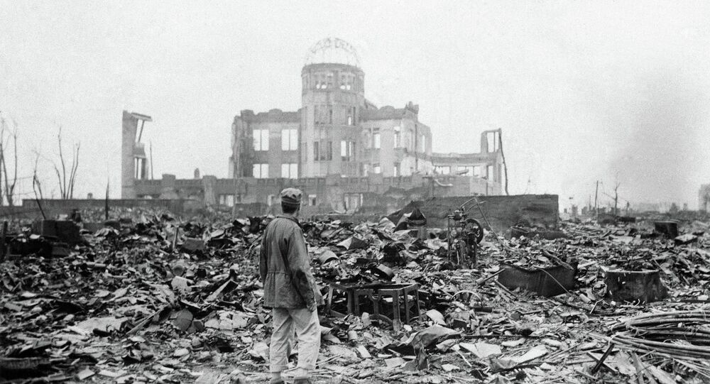 FILE - This Sept. 8, 1945 picture shows an allied correspondent standing in the rubble in front of the shell of a building that once was a movie theater in Hiroshima, Japan, a month after the first atomic bomb ever used in warfare was dropped by the US on Monday, Aug. 6, 1945