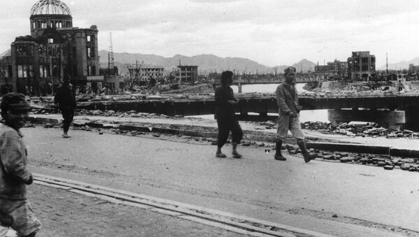 Local residents walk past the gutted Hiroshima Prefectural Industrial Promotion Hall - Sputnik International