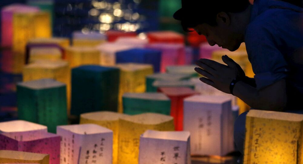 A man prays after releasing a paper lantern on the Motoyasu river facing the Atomic Bomb Dome in remembrance of atomic bomb victims on the 70th anniversary of the bombing of Hiroshima, western Japan, August 6, 2015.