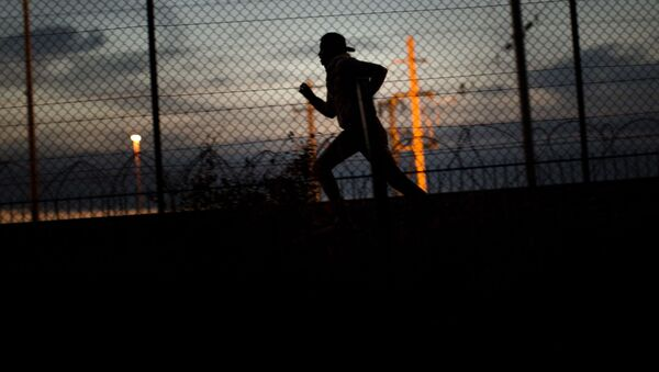 A migrant runs after crossing a fence as he attempts to access the Channel Tunnel, in Calais, northern France, Monday, Aug. 3, 2015. - Sputnik International