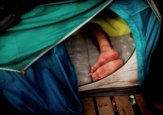 A migrant sleeps inside a tent at a camp set near Calais, northern France, Wednesday, Aug. 5, 2015.