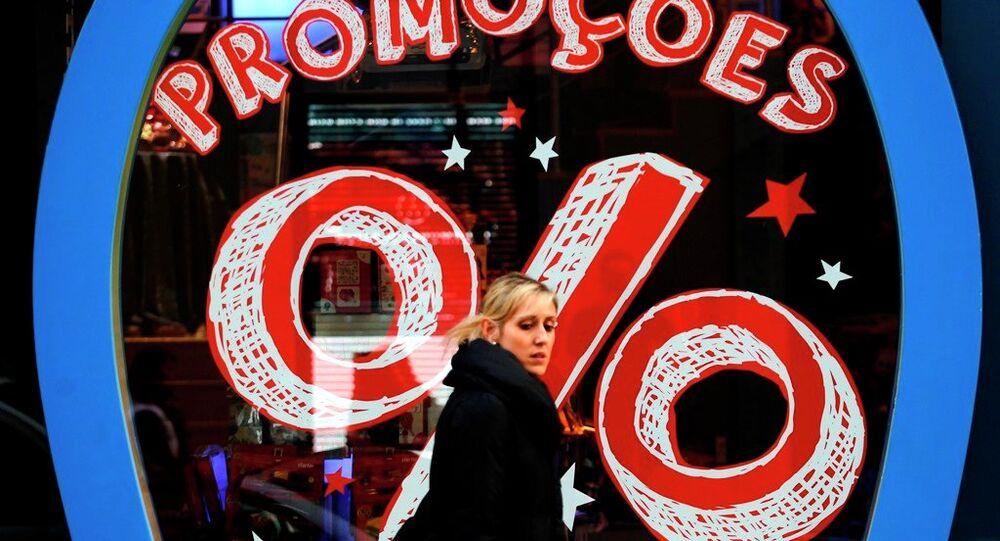 A woman walks past a shop offering discounts in downtown Lisbon, Thursday, Jan. 9, 2014.