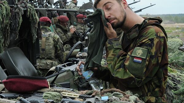 A Royal Dutch Army soldier wipes his face after the NATO Noble Jump exercise on a training range in Poland. - Sputnik International