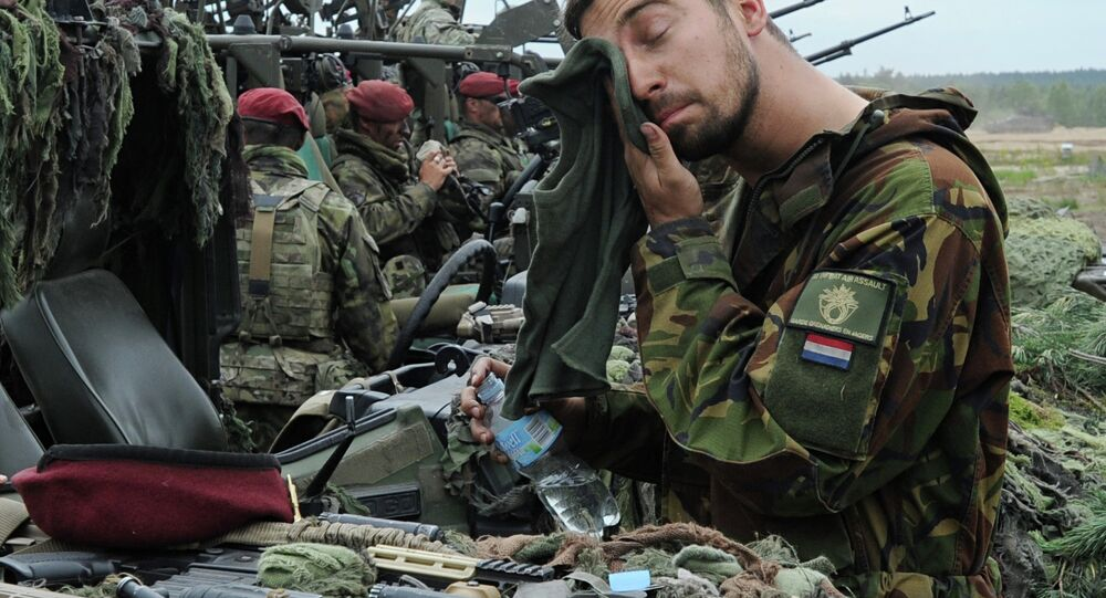 A Royal Dutch Army soldier wipes his face after the NATO Noble Jump exercise on a training range in Poland.