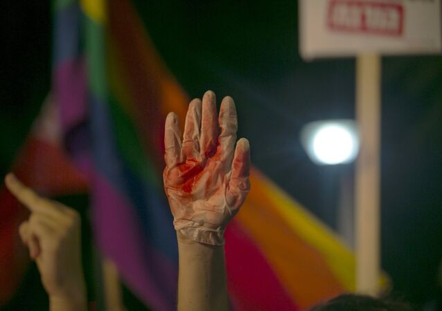 A protester holds up a glove covered in red during a protest against the violence towards the gay community in Tel Avi