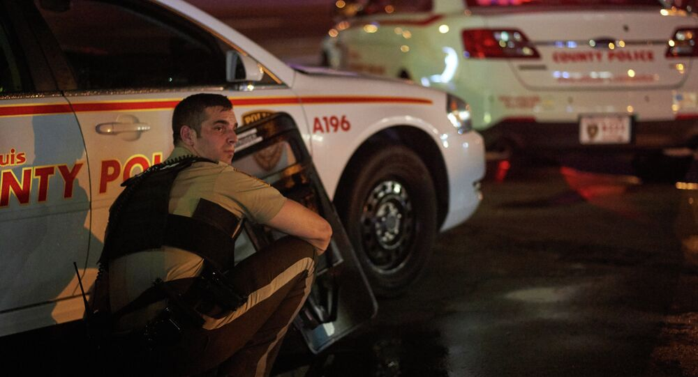 A St. Louis County police officer takes cover behind a car after shots were fired during a protest march on August 9, 2015 on West Florissant Avenue in Ferguson, Missouri