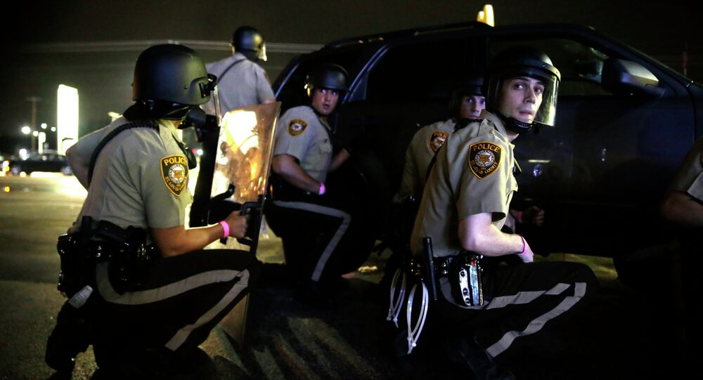 Police take cover behind a vehicle during a protest in Ferguson, Mo., Sunday, Aug. 9, 2015