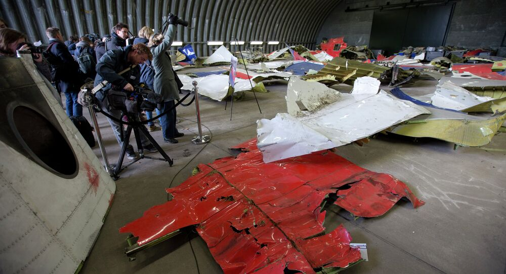 Journalists take images of parts of the wreckage of the Malaysia Airlines Flight 17 displayed in a hangar at Gilze Rijen airbase, Netherlands, Tuesday, March 3, 2015