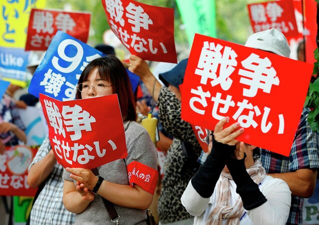 Protesters hold anti-war placards in front of the National Diet building during a rally in Tokyo