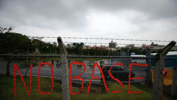 A slogan against the base is displayed on the fence enclosed U.S. Marine Corps Futenma Air Station in Ginowan on southern Japanese islands of Okinawa. File photo - Sputnik International