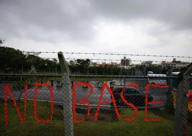 A slogan against the base is displayed on the fence enclosed U.S. Marine Corps Futenma Air Station in Ginowan on southern Japanese islands of Okinawa. File photo