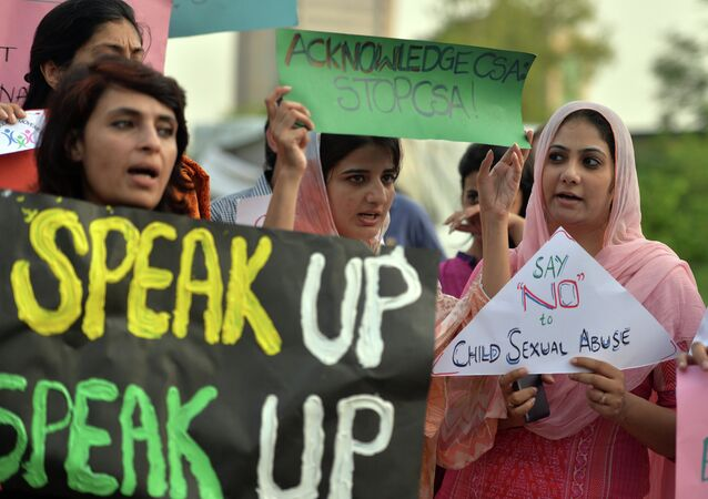 Pakistani rights activists carry placards as they shout slogans during a protest against a child sex abuse scandal in Islamabad on August 10, 2015