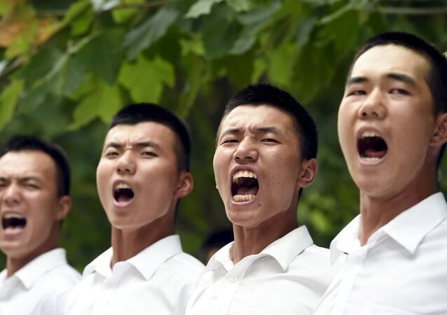 Paramilitary policemen and members of a gun salute team shout slogans as they stand in formation during a training session for a military parade to mark the 70th anniversary of the end of the World War Two, at a military base in Beijing, China, August 1, 2015