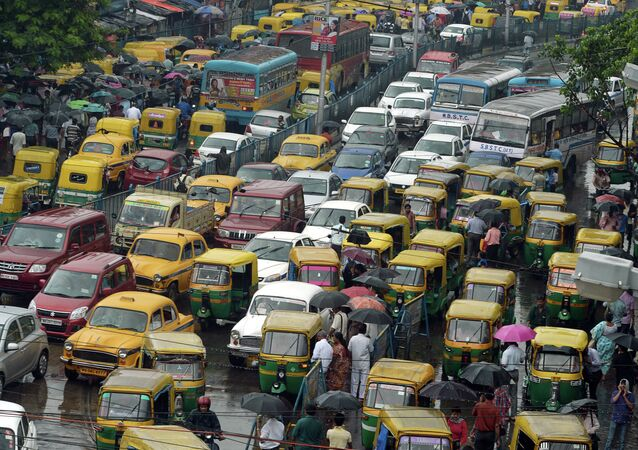 Indian commuters cross the road amid heavy rush hour traffic in Kolkata on July 31, 2015