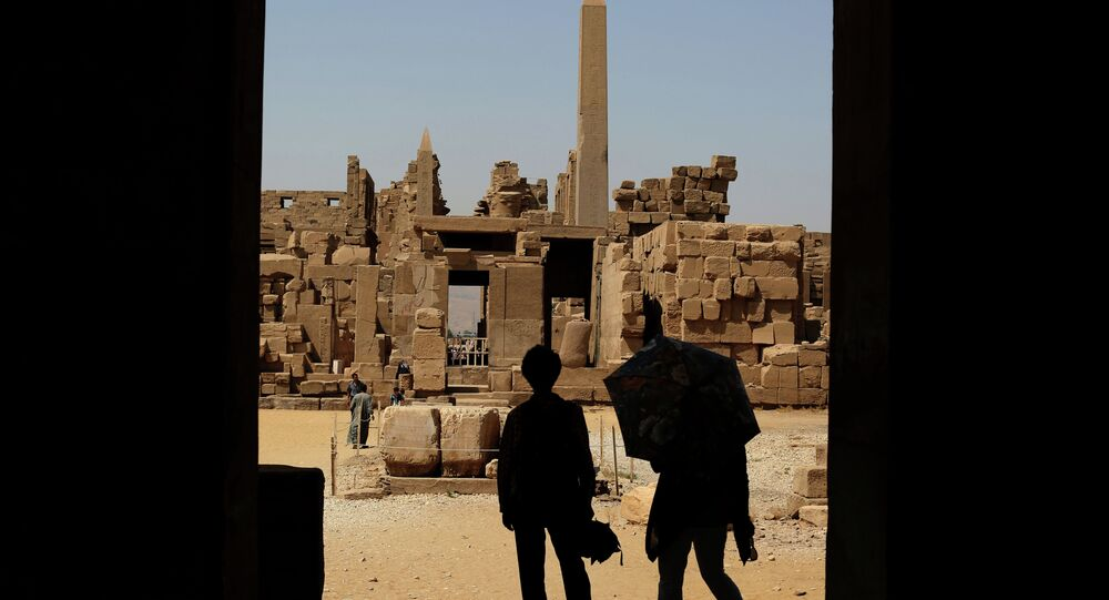 Tourists look out at the ruins of the Karnak Temple in Luxor