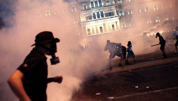 A protester clashes with riot police in front of the Greek Parliament in Athens on July 15, 2015 - Sputnik International