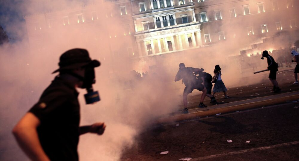 A protester clashes with riot police in front of the Greek Parliament in Athens on July 15, 2015