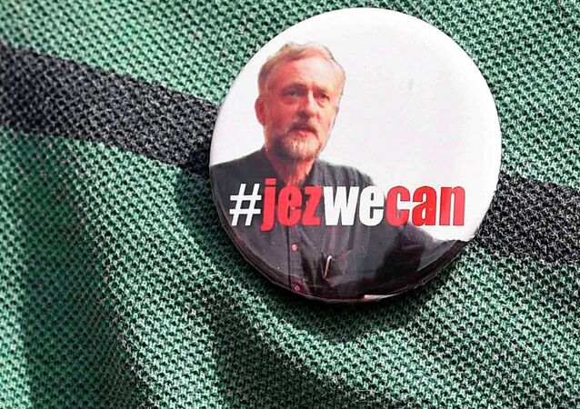 A supporter wears a campaign badge as British Labour Party politician Jeremy Corbyn arrives for a community meeting in north London August 9, 2015.