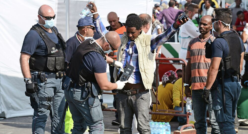 A police officer uses and hand held metal detector to check a man as he disembark from the patrol vessel Fiorillo of the Italian Coast Guard after it arrived in the port of Pozzallo on August 7, 2015 after saving some 387 migrants in the Sicilian Channel