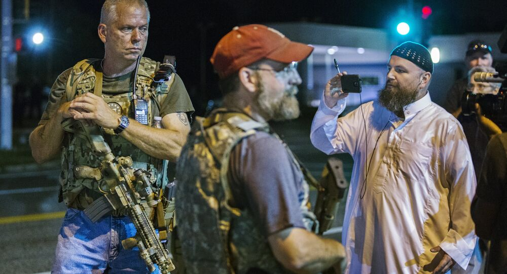Members of the Oath Keepers walk with their personal weapons on the street during protests in Ferguson, Missouri August 11, 2015.